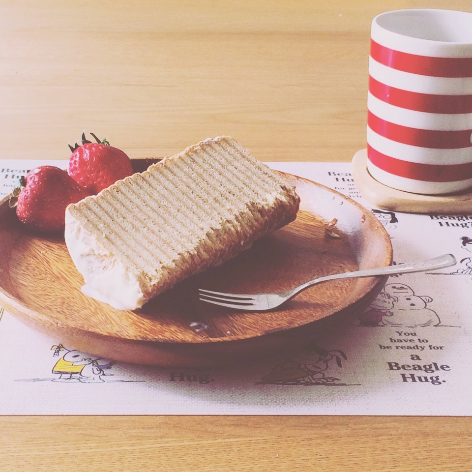 落ち着いた色の木のお皿に乗せられた黒柳徹子ケーキの写真