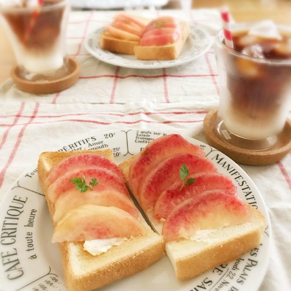 二つに分けたトーストにクリームチーズとスライスされた桃が乗っている写真