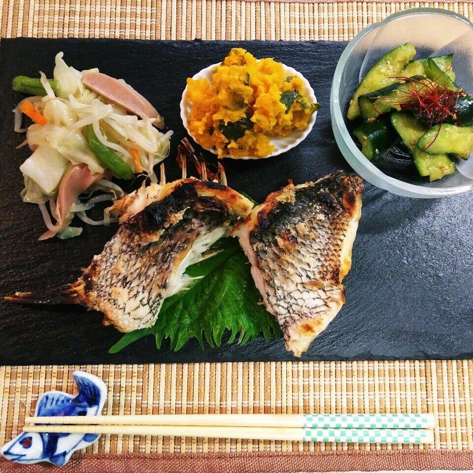 ストーンプレートに焼き魚ときゅうりやかぼちゃの小鉢が乗った写真