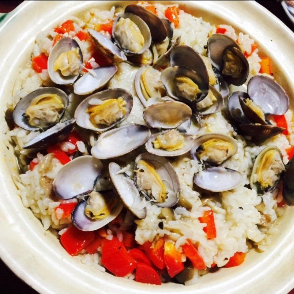 白い土鍋に入ったあさりと赤パプリカのパエリア