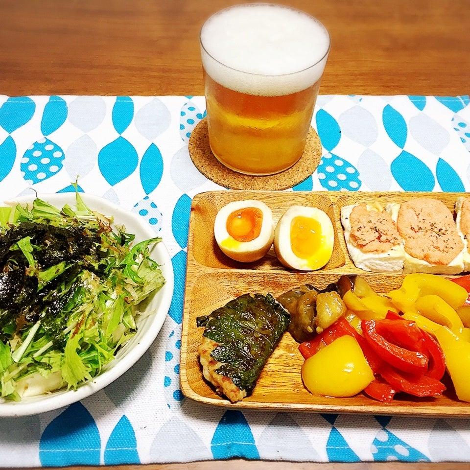 うすぐらすに注がれたビールとお皿に盛られたおつまみとサラダの写真